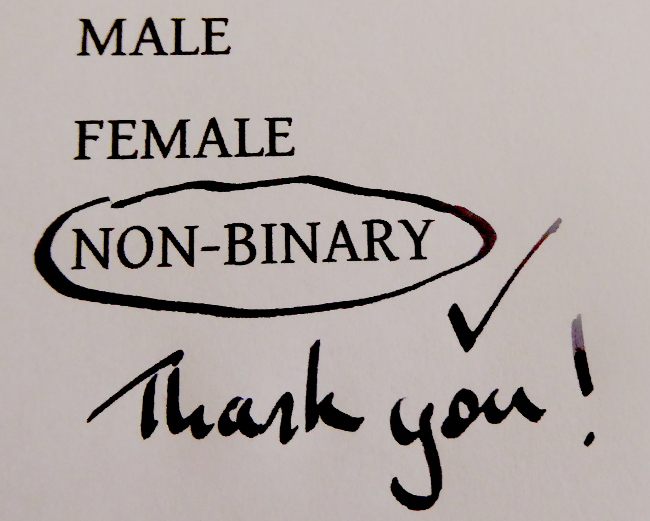 The words 'male,' 'female,' and 'non-binary' are printed on paper. The latter is circled in pen, with a checkmark and the words 'thank you!' written beside & underneath the circled selection.